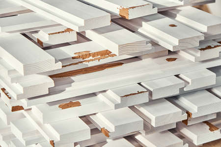 Stack of wooden bars of solid pine in white color with brown putty lie on workbench extreme closeup