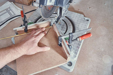 Worker cutting golden molding decorative strip for furniture facade panel on miter saw during manufacturing process