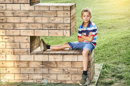 Positive little boy in striped polo t-shirt and denim shorts sits on decorative wooden installation on lush green meadow in park
