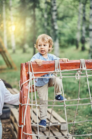Playful little boy kid climbs onto obstacle with ropes under mother control on sports ground in green sunny summer city park