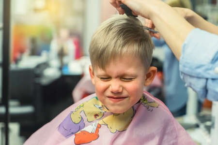 Funny little boy with screwed up eyes and cover undergoes haircut with skilled stylist in brightly lit beauty salon closeup