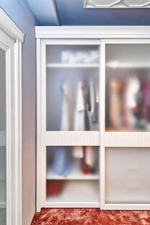 Large modern built-in cabinet with matte glass on sliding doors stands on floor covered with terracotta carpet in wooden house Stock fotó