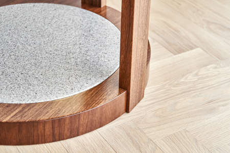 Bottom of stylish brown coffee table made of patterned veneer and solid walnut with acrylic detail on floor in room closeup
