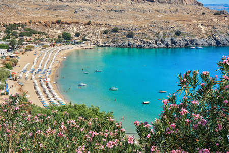 Sunbed rows on sandy Lindos beach near turquoise sea with motorboats and people swimming at sunlight on summer day in Greece Stock fotó