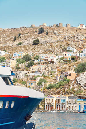 Moored large yacht on sea against historical town with old multicolored buildings scattered on hills on Symi island in Greece