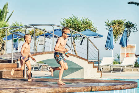Young boys with bare torsos jumping into swimming pool against sunbeds and palm trees in luxury hotel on sunny day in Greece Stock fotó