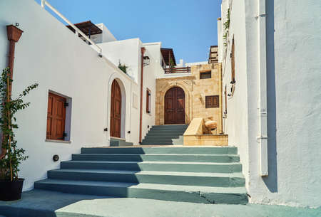 Weathered gray stairs and white historical buildings with wooden doors on Lindos town street at sunlight on summer day in Greece