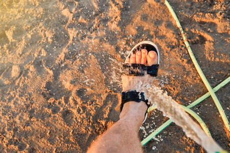 Young man tourist washing bare foot in summer sandal with hose water jet on sand Prasonisi beach under sunset light in Greece Stock fotó