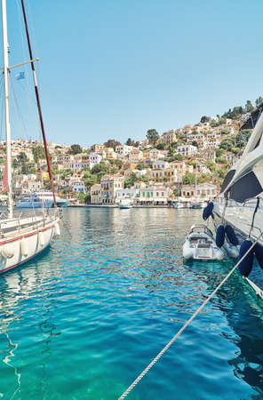 Moored sailboat and large yacht on sea against historical town with old multicolored buildings scattered on hills on Symi island in Greece Stock fotó