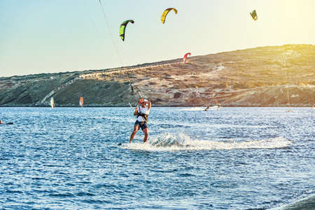Rhodes, Greece - July 08 2017: Strong sportsmen goes kitesurfing on tranquil azure sea water on Prasonisi beach at sunset on clear horizon in Greece in summer evening