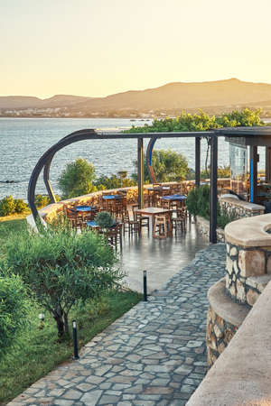 Local restaurant terrace with dining tables stone paved path and green trees against blue rippling sea at sunset on Rhodes Greece Stock fotó