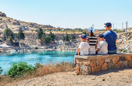 Tourist family sits on stone bench at Saint Paul's bay rocky beach with thickets by azure sea and hills with green trees under clear sky