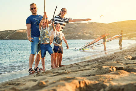 Tourist family on Prasonisi beach by blue rippling sea and kitesurfers at sunset on horizon on summer late day in Greece Stock fotó