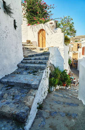 Narrow steep streets with houses whitewashed walls and blooming bushes and old stairs in historical Greek town Lindos under blue sky
