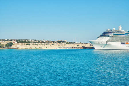 Large white tourist cruise ship on boundless blue rippling sea under clear sky near Rhodes island in Greece in summer