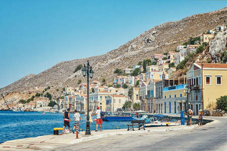 Waterfront with boats moored on azure sea berth against historical buildings in old town on Symi island on sunny day in Greece Stock fotó