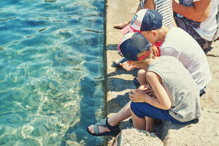 Young boys in caps sitting on transparent swimming pool barrier edge under sunlight in tourist hotel on summer day in Greece