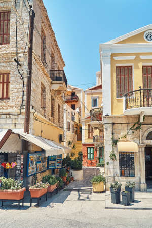 Tent of small souvenirs store located outside residential building on sunny summer day in historical town at sunlight on Symi island in Greece Stock fotó