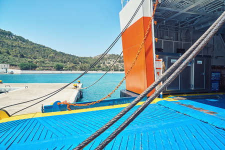 Moored large cruise ferry with open gate of rear deck against hills on Symi island under bright sunlight in Greece Stock fotó