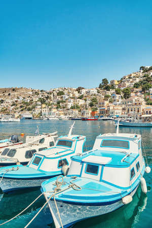Moored motorboats on azure sea with reflection against historical tourist city on bright summer day in Greece on Symi island