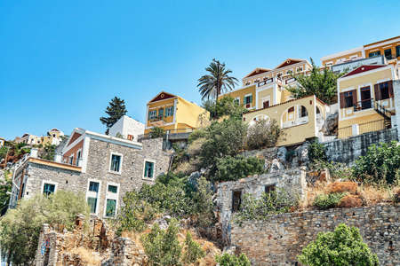 Multicolored historical buildings in old town scattered on hills on Symi island on sunny day in Greece