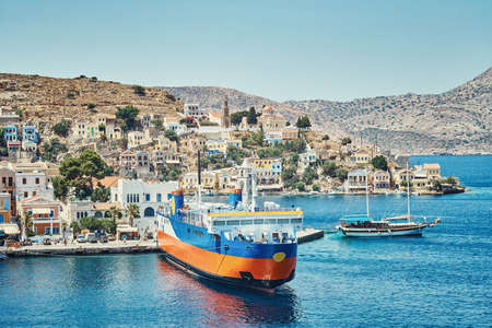 Moored large cruise ferry on sea against historical town with old multicolored buildings scattered on hills on Symi island in Greece