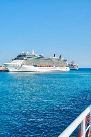 Rhodes, Greece - July 05 2017: Large white tourist cruise ship on boundless blue rippling sea under clear sky near Rhodes island in Greece in summer
