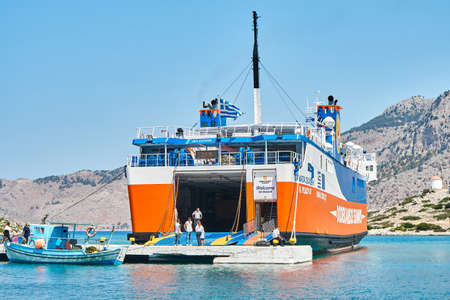 Symi, Greece - July 05 2017: Tourists leaving large cruise ferry from open gate of rear deck against mountains on Symi island under bright sunlight in Greece