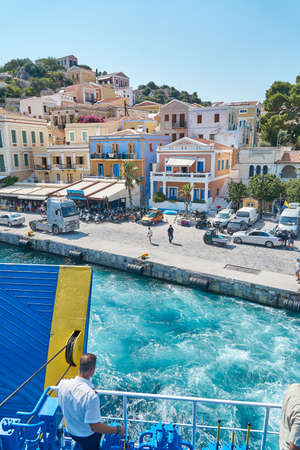 Symi, Greece - July 05 2017: Azure waving sea with foam against waterfront and historical buildings in old town under cloudless sky on Symi island in Greece