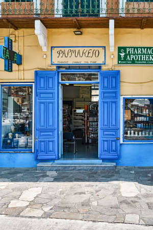 Symi, Greece - July 05 2017: Pharmacy with beautiful entrance blue doors located inside residential building on sunny summer day in historical town at sunlight on Symi island in Greece