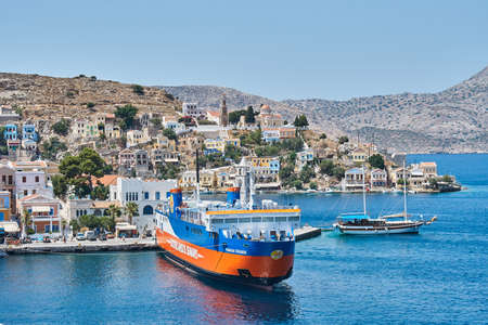 Symi, Greece - July 05 2017: Moored large cruise ferry on sea against historical town with old multicolored buildings scattered on hills on Symi island in Greece