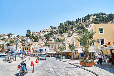 Symi, Greece - July 05 2017: Multicolored historical buildings in old town scattered on hills on Symi island on sunny day in Greece