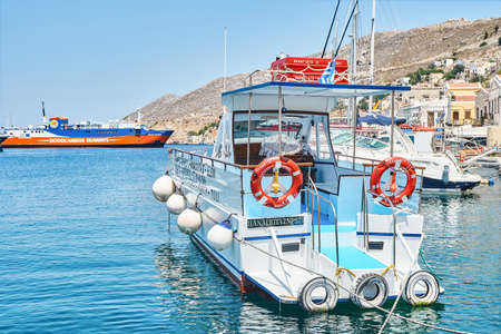 Symi, Greece - July 05 2017: Moored motorboats on azure sea with reflection against historical tourist city on bright summer day in Greece on Symi island Sajtókép