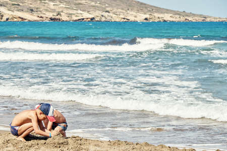 Playful little boys build sand castle on surf line against azure sea waves rolling with heavy foam on summer day on Prasonisi cape Stock fotó