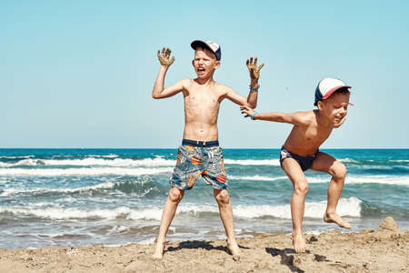 Funny joyful little brothers in shorts jump on beach wet sand against azure sea waves and blue sky on summer day on Prasonisi cape