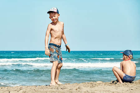 Funny joyful little brothers in shorts play on beach wet sand against azure sea waves and blue sky on summer day on Prasonisi cape