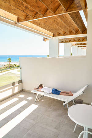 Tired little boy rests on a sun lounger on the hotel terrace with wooden bars against blue sea on clear horizon on sunny day in Greece