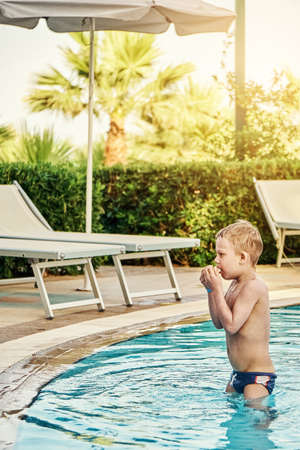 Frozen little boy stands in the children's pool and warms his hands against sunbeds and palm trees in luxury hotel on warm summer evening in Greece