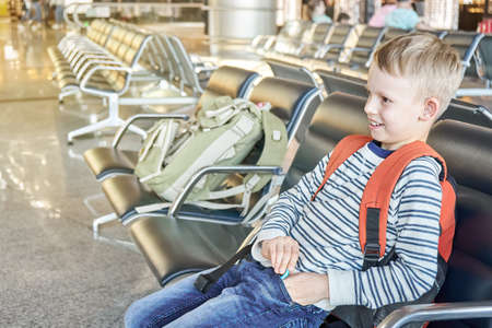 Happy junior schoolboy with orange backpack sits waiting for flight on comfortable chair in spacious hall of contemporary airport