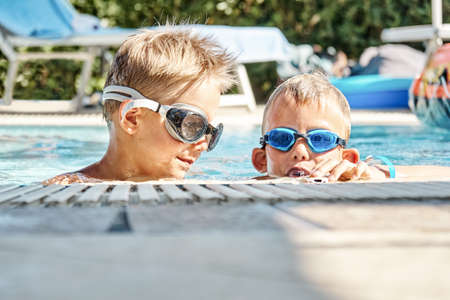 Adorable little boys brothers with swimming goggles have fun in hotel pool water on sunny summer day at resort close view Stock fotó
