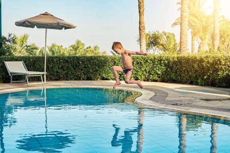 Young boy in swimming trunks jumping into childrens pool against sunbeds and palm trees in luxury hotel on warm summer evening in Greece Stock fotó