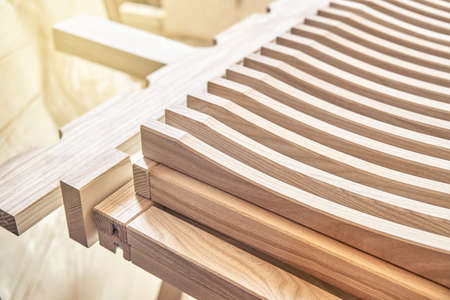 Stylish dishes drying rack made of light solid wood ash timber in modern carpentry workshop extreme close view