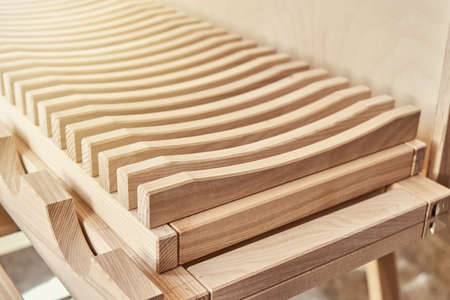 Stylish dishes drying rack made of light solid wood ash timber near plywood cabinet in modern carpentry workshop extreme close view