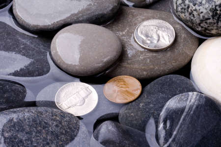 Sea water, stones and coins Stock Photo