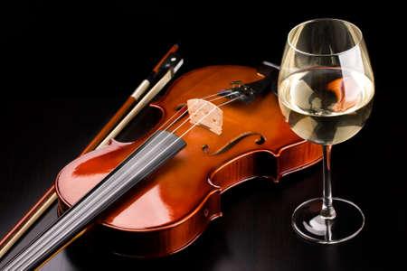 violines: Viol?n y un vaso de vino sobre la mesa Foto de archivo