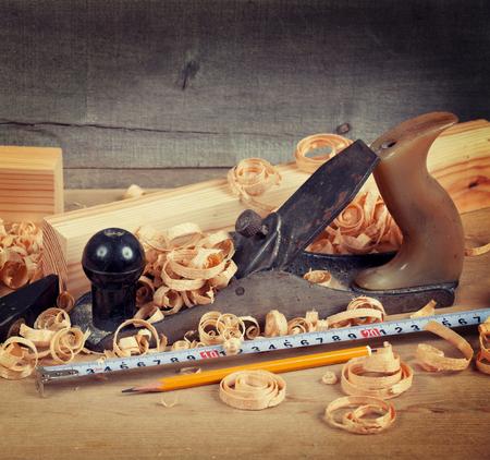 Wood planer, shavings and hand tools on board Фото со стока