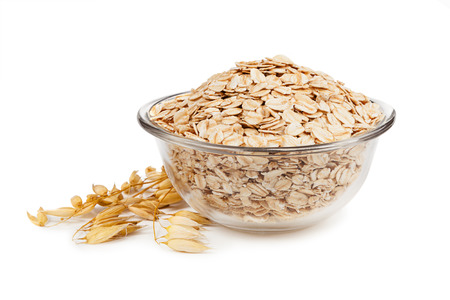 Rolled oats in a bowl isolated on white background
