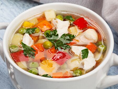Vegetable soup with chicken on table Фото со стока