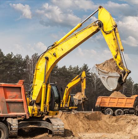 Excavators ship sand in trucks on road construction