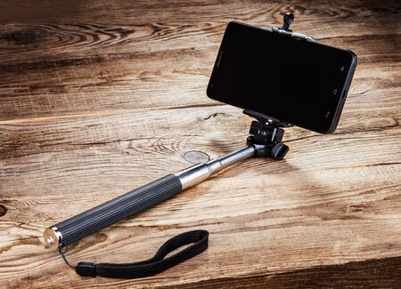 Selfie stick and smartphone on the old board Фото со стока